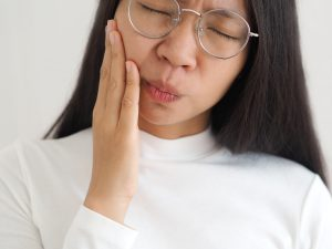 asian woman painfully grasping cheek in need of TMJ treatment